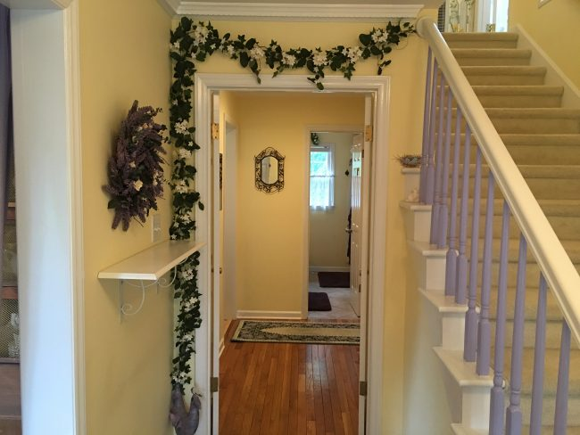 Step through the front door into the foyer of GardenSpirit with soft yellow walls and a floral motif.