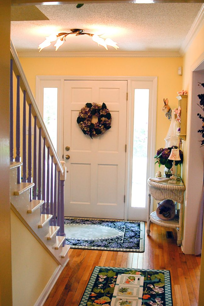 Foyer with a purple staircase and garden rugs.